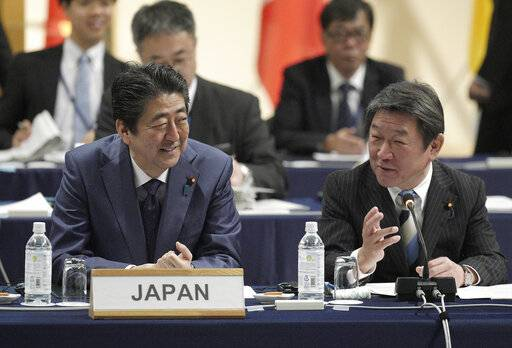 Japan's Prime Minister Shinzo Abe, left, and Minister of Economy, Trade, Industry Toshimitsu Motegi, right, share a light moment during an opening session of the Comprehensive and Progressive Trans-Pacific Partnership (CPTPP) in Tokyo, Saturday, Jan. 19, 2019. Trade ministers of a Pacific Rim trade bloc are meeting in Tokyo, gearing up to roll out and expand the market-opening initiative. (AP Photo/Eugene Hoshiko)