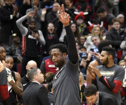 Miami Heat guard Dwyane Wade (3) gestures to the crowd after being honored during the first half of an NBA basketball game against the Chicago Bulls, Saturday, Jan. 19, 2019, in Chicago.
