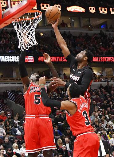 Miami Heat guard Dwyane Wade (3) goes to the basket as Chicago Bulls forward Bobby Portis (5) and guard Shaquille Harrison (3) defend during the first half of an NBA basketball game Saturday, Jan. 19, 2019, in Chicago.