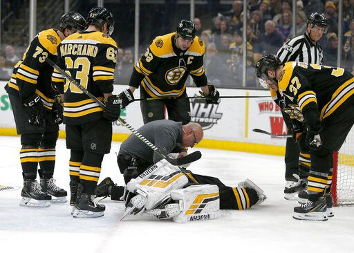 Boston Bruins goaltender Tuukka Rask (40) is attended to by medical personnel as his teammates look on after taking a hit on a goal by New York Rangers center Filip Chytil during the first period of an NHL hockey game, Saturday, Jan. 19, 2019, in Boston.