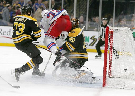 New York Rangers center Filip Chytil (72) collides with Boston Bruins goaltender Tuukka Rask (40) as he scores a goal, next to Charlie McAvoy (73) during the first period of an NHL hockey game Saturday, Jan. 19, 2019, in Boston. Rask left the game with an injury after the goal.