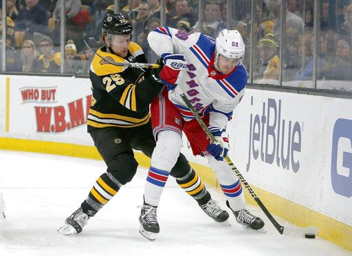 Boston Bruins defenseman Brandon Carlo (25) and New York Rangers right wing Pavel Buchnevich (89) battle for the puck along the boards during the first period of an NHL hockey game, Saturday, Jan. 19, 2019, in Boston.