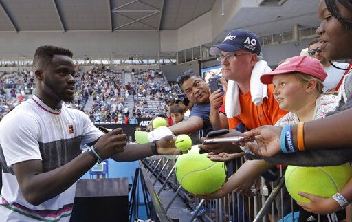 United States' Frances Tiafoe signs autographs after defeating Bulgaria's Grigor Dimitrov in their fourth round at the Australian Open tennis championships in Melbourne, Australia, Sunday, Jan. 20, 2019.