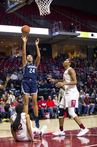 Connecticut's Napheesa Collier, center, shoots the ball with Temple's Emani Mayo, left, and Shantay Taylor, right, defending during the first half of an NCAA college basketball game, Saturday, Jan. 19, 2019, in Philadelphia. (AP Photo/Chris Szagola)