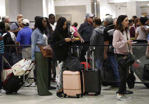 FILE- In this Jan. 18, 2019, file photo passengers wait in line at a security checkpoint at Miami International Airport in Miami. While security screeners and air traffic controllers have been told to keep working, Federal Aviation Administration safety inspectors weren't, until the agency began recalling some Jan. 12. About 2,200 of the more than 3,000 inspectors are now back on the job, overseeing work done by airlines, aircraft manufacturers and repair shops. The government says they're doing critical work but forgoing such tasks as issuing new pilot certificates.(AP Photo/Lynne Sladky, File)