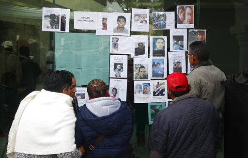 People look at photographs of people who are missing since the pipeline accident in Tlahuelilpan, Mexico, Sunday Jan. 20, 2019. A massive fireball that engulfed locals scooping up fuel spilling from a pipeline ruptured by thieves in central Mexico killed dozens of people and badly burned dozens more on Jan. 18.