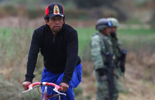 A cyclist passes soldiers who guard the site where a gas pipeline exploded two days prior, in the village of Tlahuelilpan, Mexico, Sunday Jan. 20, 2019. A massive fireball that engulfed locals scooping up fuel spilling from a pipeline ruptured by thieves in central Mexico killed dozens of people and badly burned dozens more on Jan. 18.