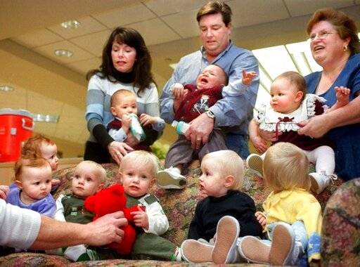 In this Jan. 10, 2019 photo, Darrin Dohme, center, has his hands full with son Dylan, as wife Julle, left, holds Jacob and their triplets' godmother, Tena Fowler of right, holds Caroline during a first-anniversary reunion of the 'Magnificent Nine' - three sets of twins and a set of triplets all born in the same 24-hour period on Jan. 9-10, 2001, at Carle Foundation Hospital in Urbana - on Thursday, Jan. 10, 2002, in Urbana, Ill. Joining them on the couch are, from left, twin sisters Mariya and Taelyn Harris of Georgetown; twin brothers David and Daniel Ekstam of Champaign; and Quinn Gard and his twin sister, Carrigan, of Danville all frrom Illinois. (Heather Coit/The News-Gazette via AP )