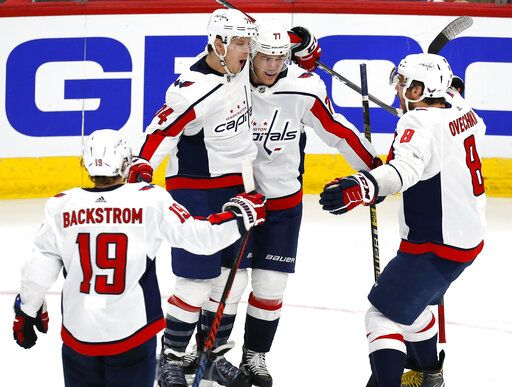 Second from left Washington Capitals defenseman John Carlson (74) celebrates with teammates after his goal against the Chicago Blackhawks, during the third period of an NHL hockey game Sunday, Jan. 20, 2019, in Chicago.