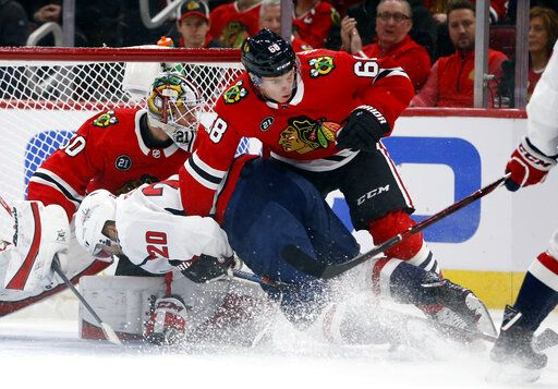 Washington Capitals center Lars Eller (20) is pushed down to the ice by Chicago Blackhawks defenseman Slater Koekkoek (68) during the first period of an NHL hockey game Sunday, Jan. 20, 2019, in Chicago.