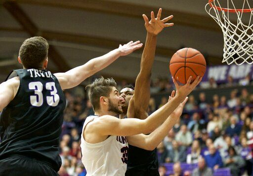 Gonzaga forward Killian Tillie, center, shoots past Portland center Theo Akwuba, right, and forward Jacob Tryon, left, during the first half of an NCAA college basketball game in Portland, Ore., Saturday, Jan. 19, 2019.