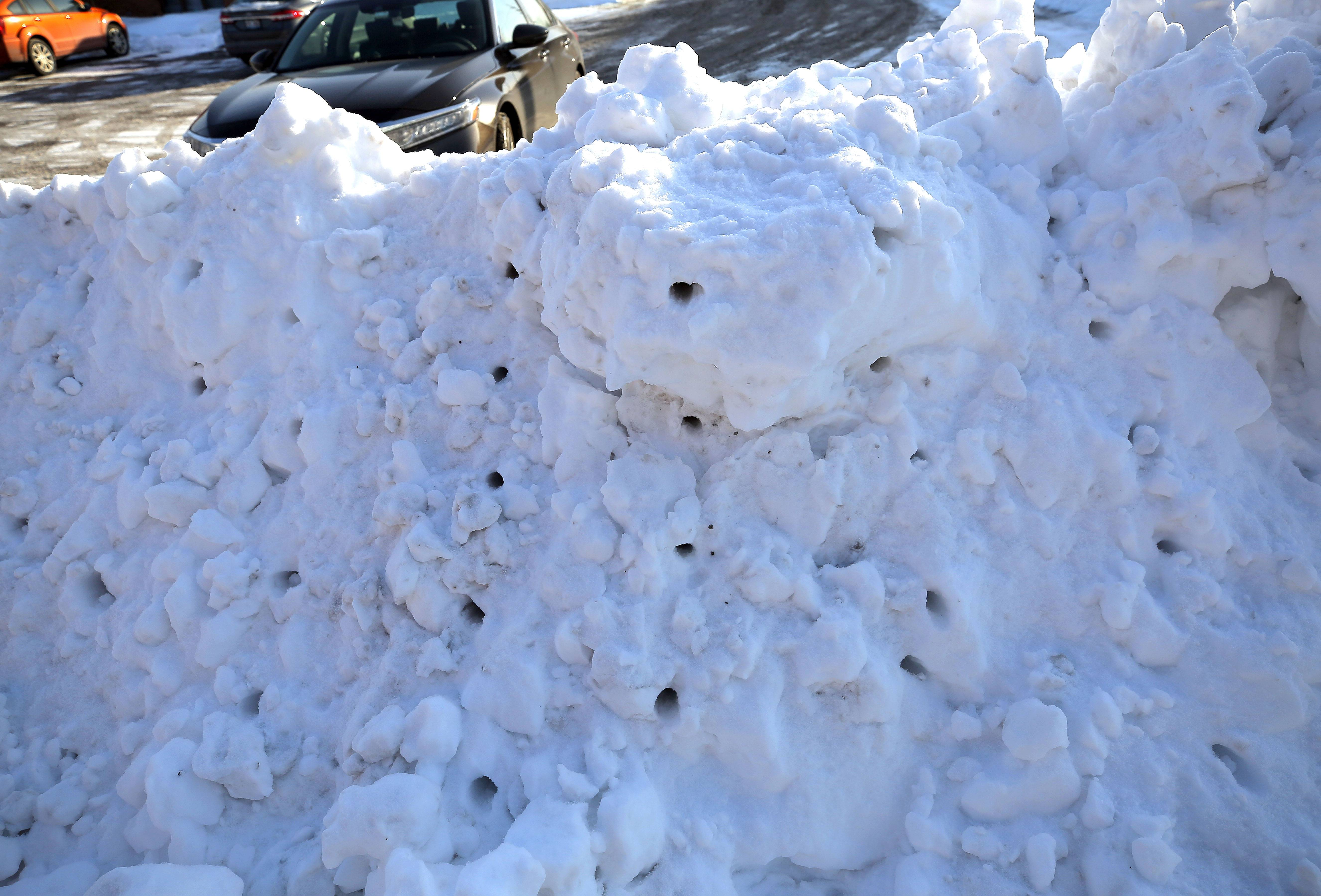 Holes in a snow bank show where rescuers searched for a child who died after a snow fort collapsed on her at Rothem Church in Arlington Heights.
