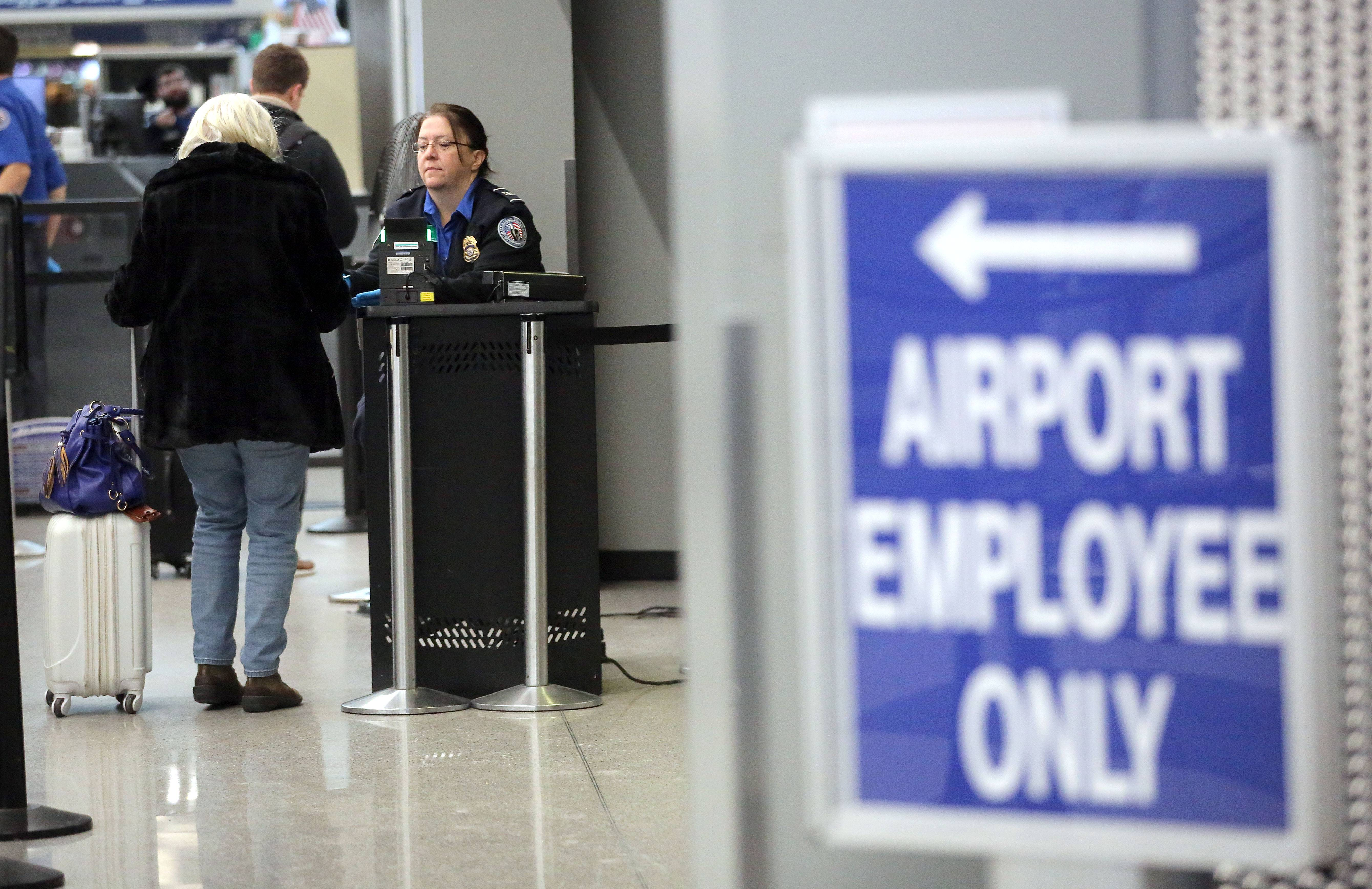 An unpaid TSA agent helps a traveler at O'Hare International Airport in Chicago last week.