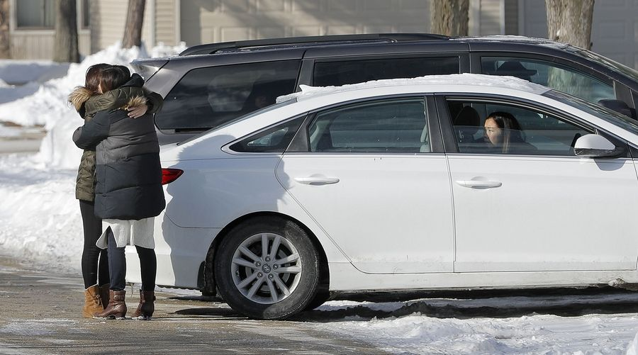 People hug in front of the Elk Grove Village house of 12-year-old Esther Jung on Monday afternoon. She died Sunday when a snow pile collapsed on her outside her father's Arlington Heights church.