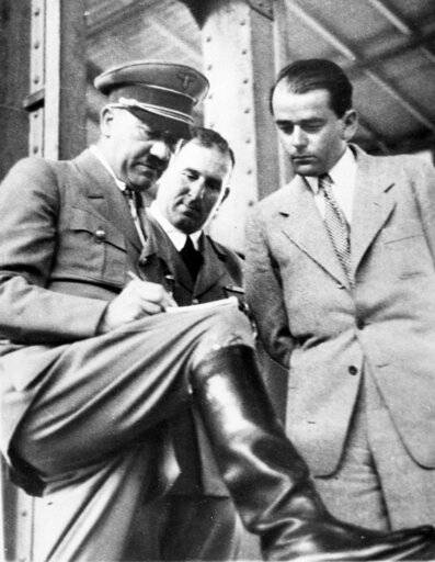 "FILE - In this file photo dated Feb. 19, 1937, German Chancellor Adolf Hitler, left, discusses plans for building a convention hall at Nuremberg with Lord Mayor Willy Liebel, centre, and Prof. Albert Speer, right, at Nuremberg, Germany. Hilde Schramm inherited several paintings collected by her father, Hitler's chief architect and Armaments Minister Albert Speer, but she didn't want them. Instead, Schramm sold them and used the money to start the Zurueckgeben foundation, translated to ""return� or ""give back�, for which she is receiving an Obermayer German Jewish History Award on Monday Jan. 21, 2019. (AP Photo, File)"