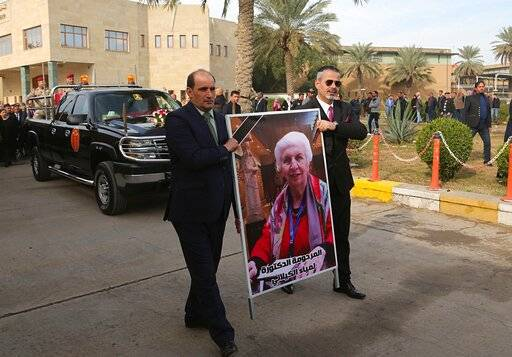 Mourners transport the flag-draped coffin of Iraqi archaeologist, Lamia al-Gailani, seen in the poster, for burial during her funeral procession in the National Museum in Baghdad, Iraq, Monday, Jan. 21, 2019. Iraq is mourning the loss of a beloved archaeologist who helped rebuild her country's leading museum in the aftermath of the U.S. invasion in 2003. (AP Photo/Khalid Mohammed)