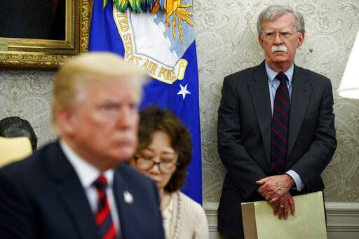 FILE - In this May 22, 2018, file photo, U.S. President Donald Trump, left, meets with South Korean President Moon Jae-In in the Oval Office of the White House in Washington, as national security adviser John Bolton, right, watches. In President Donald Trump's Washington, matters of war and peace are decided in 280-character bursts. It's up to John Bolton to massage them into a foreign policy. (AP Photo/Evan Vucci, File)