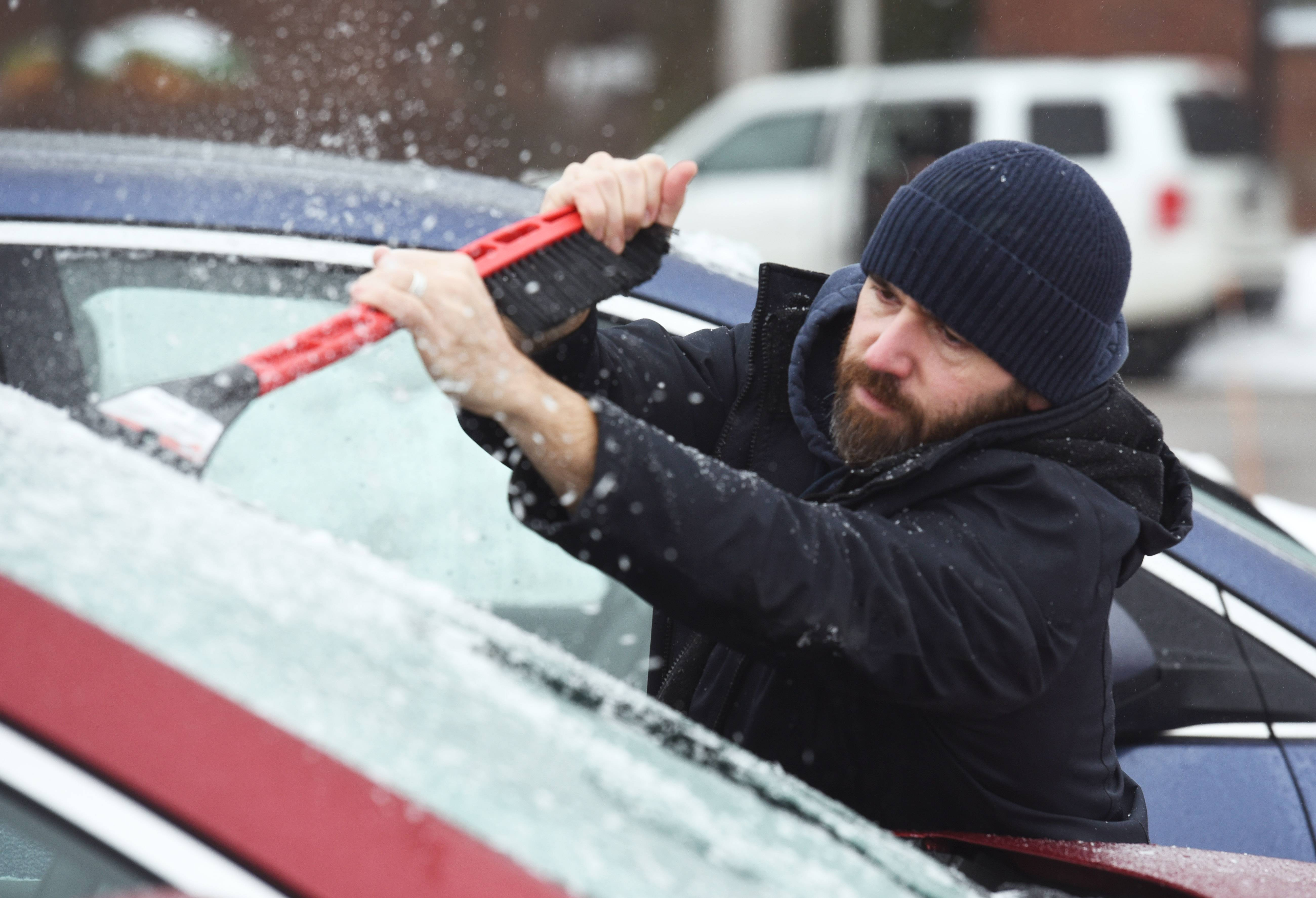 Michael Weaver of Libertyville scrapes ice off his windshield Tuesday at the Cook Park Library in Libertyville. Freezing rain moved into the area Tuesday morning.