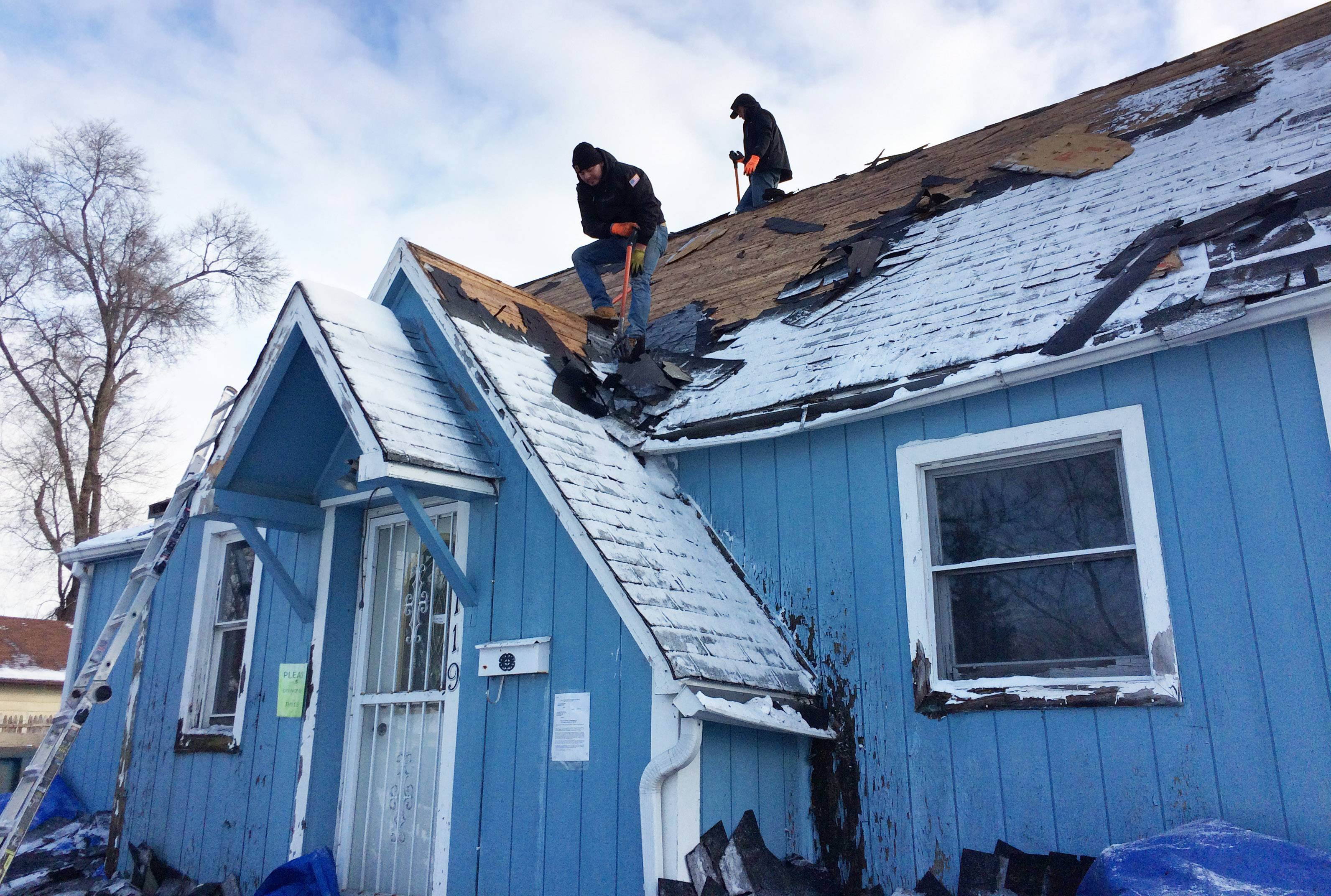 Roofers remove old shingles as part of a project to rehab an abandoned house on the 100 block of Bellevue Drive in Round Lake Park. It's part of a new village initiative to improve neighborhoods and eliminate nuisance properties.