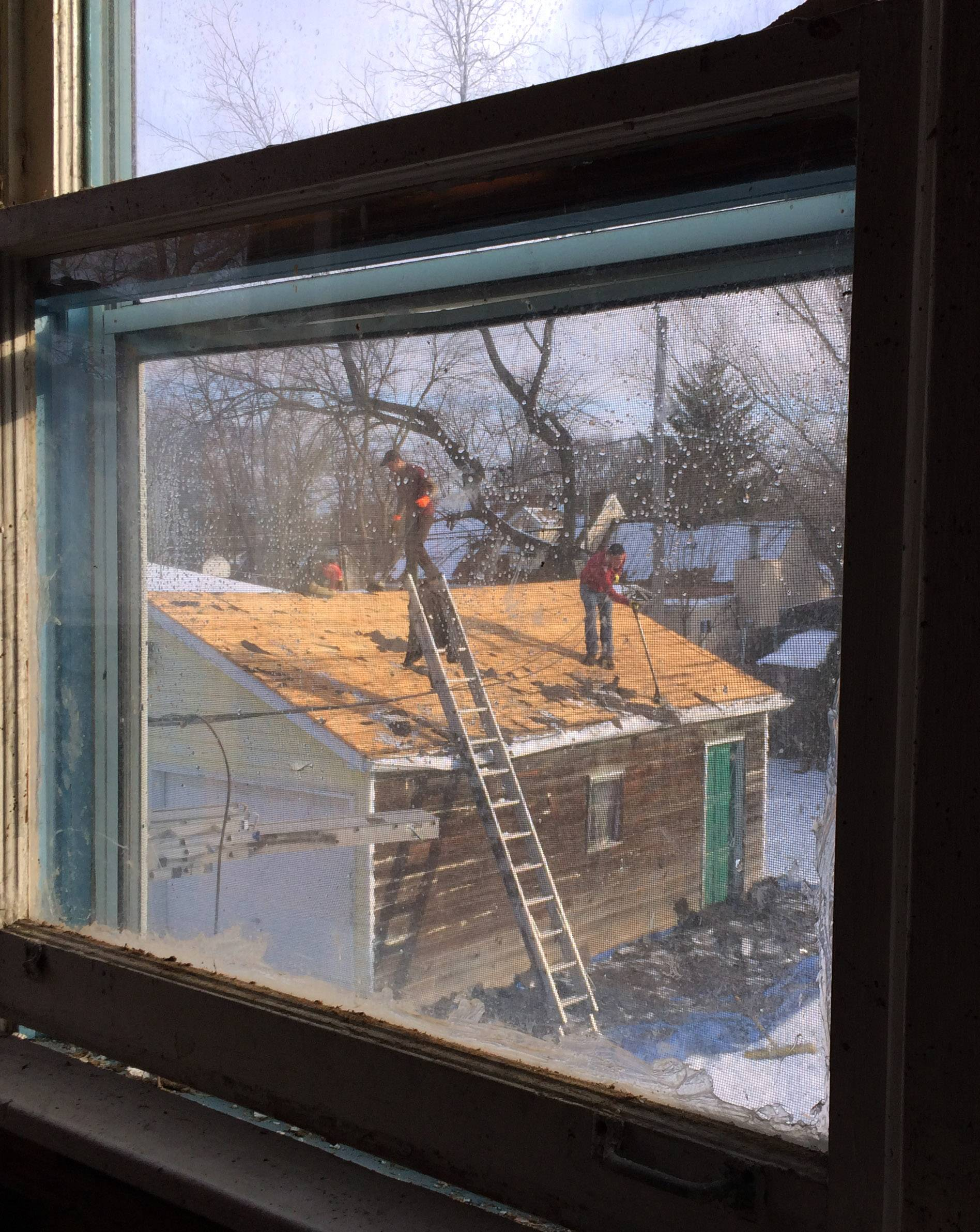 The view from inside a home on the 100 block of Bellevue Drive in Round Lake Park as roofers work on the garage.