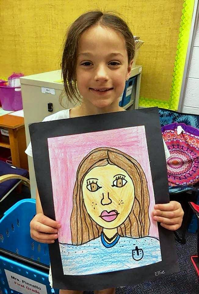 Ellie Labowicz holds her self-portrait. Ellie's artwork is part of the 2018-2019 Illinois Art Education Association's Student Art Show at the Palatine Library during February.