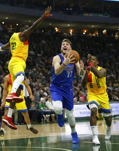 Dallas Mavericks' Luka Doncic (77) shoots between Milwaukee Bucks' Eric Bledsoe (6) and Tony Snell during the first half of an NBA basketball game Monday, Jan. 21, 2019, in Milwaukee.