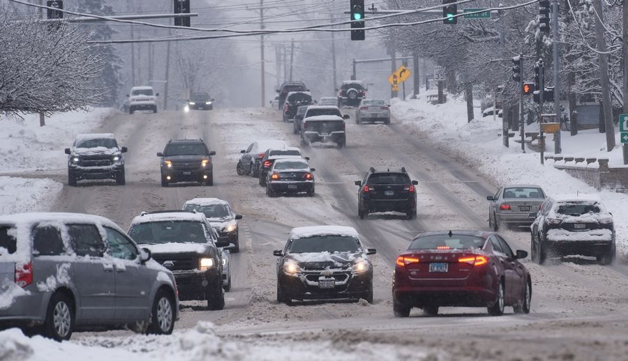 Commuters travel along a snow-packed Route 14 in Cary Wednesday.