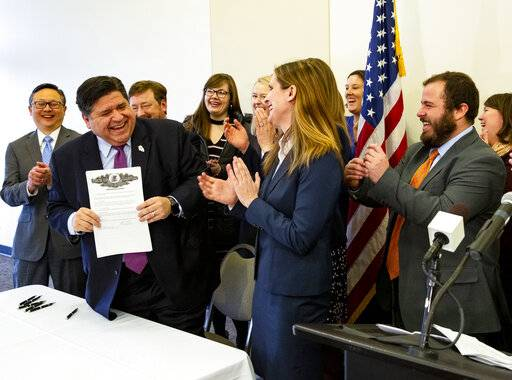 Illinois Gov. J.B. Pritzker, left, with environmental advocates cheering, holds an executive order he signed committing Illinois to the U.S. Climate Alliance Wednesday, Jan. 23, 2019, at Erin's Pavilion in Springfield, Ill. (Rich Saal/The State Journal-Register via AP)