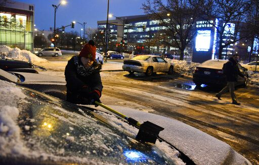 Meredith Davis scrapes off her car as snow and freezing rain arrived on Tuesday, Jan. 22, 2019, in Chicago.