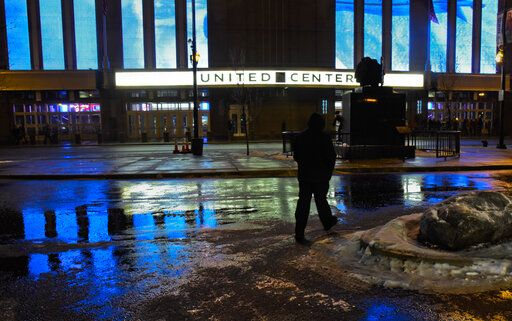 A fan braves the snow and freezing rain as he arrives at the United Center for a Chicago Blackhawks game against the New York Islanders on Tuesday, Jan. 22, 2019, in Chicago.