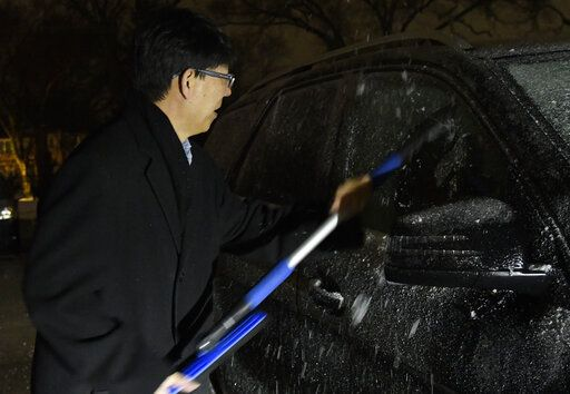 Hongxin Dong scraps ice off his car Tuesday, Jan. 22, 2019, in Evanston, Ill. Fatal accidents involving vehicles sliding off icy roadways have been reported in Wisconsin, Kansas and Illinois, and more than 500 flights have been cancelled at Chicago's two major airports.