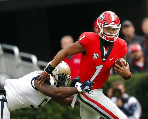 FILE - In this Saturday, Nov. 24, 2018, file photo, Georgia quarterback Justin Fields (1) tries to escape from Georgia Tech linebacker Victor Alexander (9) in the second half of an NCAA college football game in Athens, Ga. The NCAA quietly made a big change last year that helped quarterback Shea Patterson play for Michigan and will determine whether Justin Fields is eligible this fall at Ohio State.