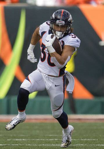 FILE - In this Dec. 2, 2018, file photo, Denver Broncos running back Phillip Lindsay (30) runs with the ball during the first half of the NFL football game against the Cincinnati Bengals, in Cincinnati. He didn't get invited to the NFL combine and wasn't selected in the NFL draft. Then, an injury threatened to keep Phillip Lindsay from the spoils of his sensational season, the Pro Bowl. Although he won't be playing, the Denver Broncos rookie running back is attending the league's annual all-star game as a social media correspondent for the league.