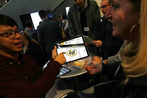 People watch real-time puck and player tracking technology on a tablet during an NHL hockey game between the Vegas Golden Knights and the San Jose Sharks in Las Vegas, Thursday, jan. 10, 2019. The NHL for the first time has tested real-time puck and player tracking in regular-season games with the aim of having it ready for the 2019-20 season. Microchips were added to players' shoulder pads and fitted inside specially designed pucks for two Vegas Golden Knights home games this week: Tuesday against the New York Rangers and Thursday against the San Jose Sharks. Antennas stationed around the arena tracked the players and the puck through radio frequencies and beamed the data to a suite where league and Players' Association executives and representatives from 20 teams and various technology firms, sports betting companies and TV rights holders were on hand for the two nights of testing.