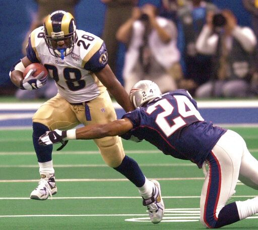 File-This Feb. 3, 2002, file photo shows St. Louis Rams running back Marshall Faulk (28) fending of New England Patriots cornerback Ty Law (24) during first-quarter play of Super Bowl XXXVI in New Orleans. The Greatest Show On Turf. When the St. Louis Rams were partying like it was 1999, they scored 526 points; ranked first in yards, yards passing, and TD passes; and were second in yards rushing per attempt. Faulk rushed for 1,381 yards and seven touchdowns, caught 87 balls for 1,087 yards, with five more TDs, and was the NFL Offensive Player of the Year for the first of three straight seasons.