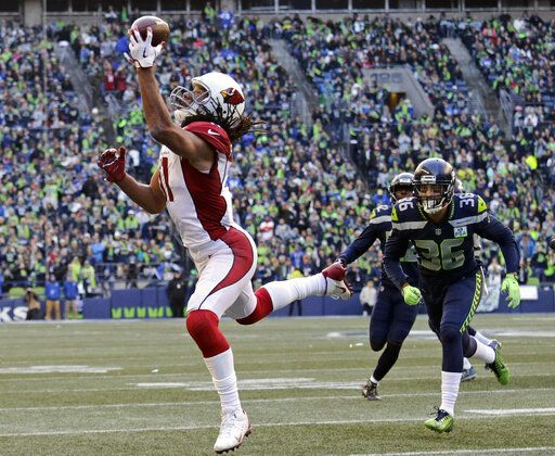 "FILE - In this Dec. 30, 2018, file photo, Arizona Cardinals' Larry Fitzgerald, left, snags a one-handed touchdown pass against the Seattle Seahawks during the first half of an NFL football game, in Seattle. Star receiver Larry Fitzgerald is returning to the Arizona Cardinals for a 16th NFL season. The Cardinals announced Wednesday, Jan. 23, 2019, that they signed the 35-year-old Fitzgerald to a one-year contract. Team president Michael Bidwell says, ""No player has meant more to this franchise or this community than Larry Fitzgerald.�"