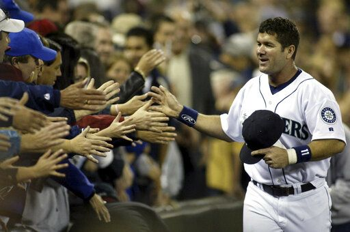 File-This Oct. 2, 2004, file photo shows Seattle Mariners Edgar Martinez high fiving Mariner fans as he runs the track surrounding the infield during Edgar Martinez Day in Seattle. Martinez was a .312 hitter over 18 seasons with Seattle. He got 85.4 percent in his 10th and final try on the writers' ballot. He and Baines will join 2014 inductee Frank Thomas as the only Hall of Famers to play the majority of their games at designated hitter. David Ortiz will be eligible in 2022.