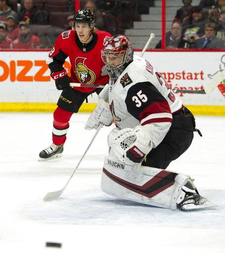 Arizona Coyotes goaltender Darcy Kuemper (35) and Ottawa Senators left wing Ryan Dzingel keep an eye on the puck as it deflects wide of the net during the second period of an NHL hockey game in Ottawa, Tuesday, Jan. 22, 2019. (Adrian Wyld/The Canadian Press via AP)