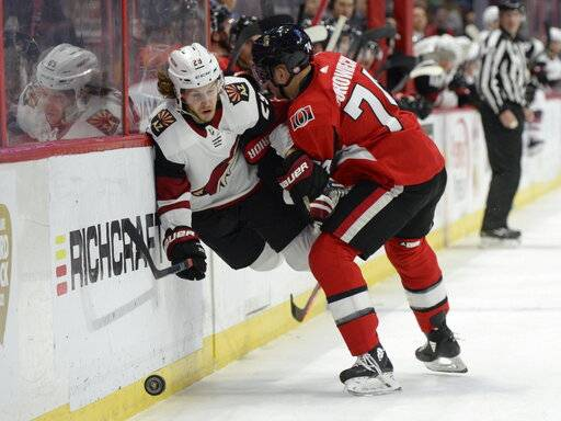 Ottawa Senators' Mark Borowiecki (74) sends Arizona Coyotes' Mario Kempe into the boards during first period NHL action in Ottawa, Tuesday, Jan. 22, 2019.  (Adrian Wyld/The Canadian Press via AP)