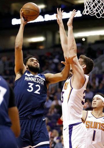 Minnesota Timberwolves center Karl-Anthony Towns (32) shoots over Phoenix Suns forward Dragan Bender during the first half of an NBA basketball game, Tuesday, Jan. 22, 2019, in Phoenix.