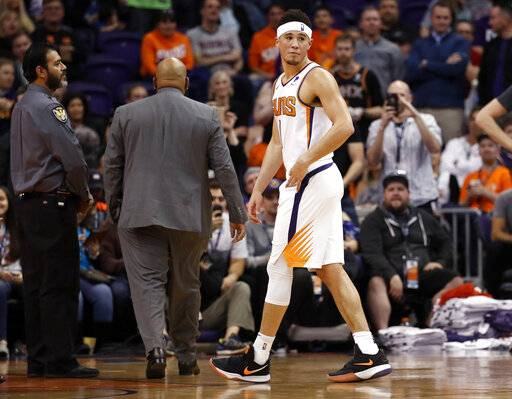 Phoenix Suns guard Devin Booker (1) leaves the game after being ejected during the second half of an NBA basketball game against the Minnesota Timberwolves, Tuesday, Jan. 22, 2019, in Phoenix.