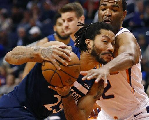 Minnesota Timberwolves guard Derrick Rose (25) tries to slip past Phoenix Suns forward T.J. Warren, right, during the first half of an NBA basketball game, Tuesday, Jan. 22, 2019, in Phoenix.