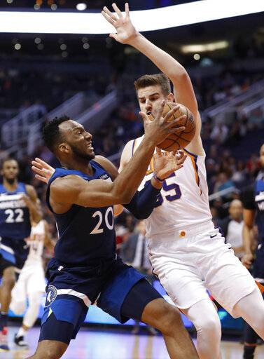 Minnesota Timberwolves guard Josh Okogie (20) drives to the basket as Phoenix Suns forward Dragan Bender (35) defends during the first half of an NBA basketball game, Tuesday, Jan. 22, 2019, in Phoenix.