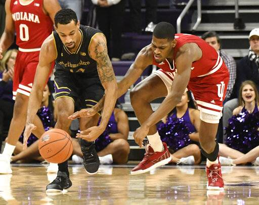 Northwestern guard Ryan Taylor, left, and Indiana guard Aljami Durham, right, go for a loose ball during the first half of an NCAA college basketball game Tuesday, Jan. 22, 2019, in Evanston, Ill.