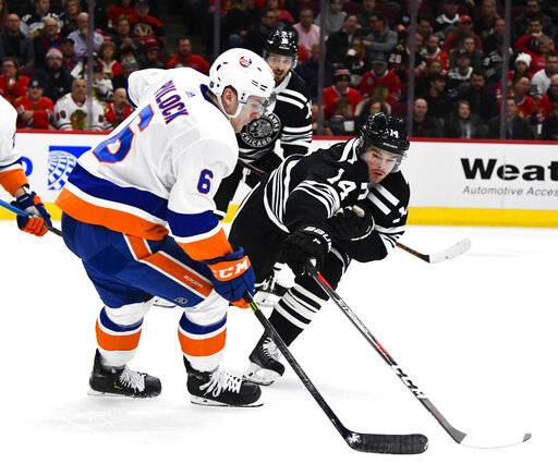 New York Islanders defenseman Ryan Pulock (6) fights for the puck against Chicago Blackhawks left wing Chris Kunitz (14) during the first period of an NHL hockey game on Tuesday Jan. 22, 2019, in Chicago.