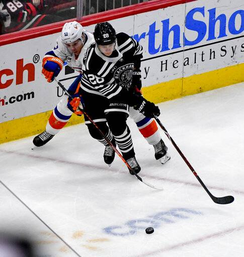 New York Islanders center Casey Cizikas (53) and Chicago Blackhawks defenseman Henri Jokiharju (28) fight for the puck during the second period of an NHL hockey game on Tuesday Jan. 22, 2019, in Chicago.