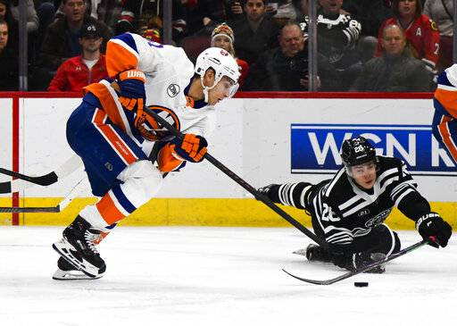New York Islanders center Valtteri Filppula, left, fights for the puck with Chicago Blackhawks defenseman Henri Jokiharju (28) during the first period of an NHL hockey game on Tuesday Jan. 22, 2019, in Chicago.