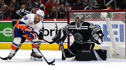 New York Islanders lineman Anthony Beauvillier (18) shoots against Chicago Blackhawks defenseman Slater Koekkoek (68) and goaltender Cam Ward (30) during the first period of an NHL hockey game on Tuesday Jan. 22, 2019, in Chicago.