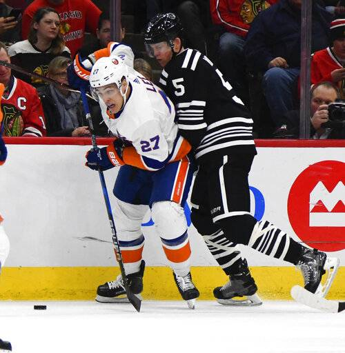 New York Islanders lineman Anders Lee (27) fights for the puck against Chicago Blackhawks defenseman Connor Murphy (5) during the first period of an NHL hockey game on Tuesday Jan. 22, 2019, in Chicago.