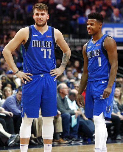 Dallas Mavericks Luka Doncic (77) of Germany and teammate Dennis Smith Jr. (1) share a laugh during the first half of an NBA basketball game against the LA Clippers in Dallas, Tuesday, Jan. 22, 2019.
